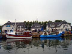 Fischerboote im Hafen von Vitte. Rechts die Fischgaststätte, in der Mitte ein Souvenirshop, links die Fischhalle.